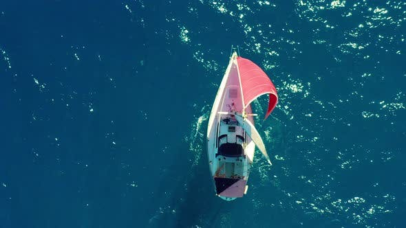 Thumbnail for Aerial View. Beautiful Sailing Yacht with a Red Sail Is Sailing on the Emerald Sea on a Sunny Day.