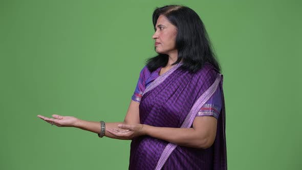 Thumbnail for Mature Beautiful Indian Woman Showing Something While Wearing Sari Traditional Clothes