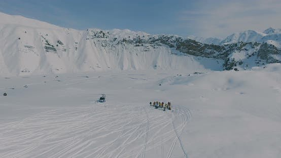 Cover Image for Aerial landing near a helicopter and a group of skiers and snowboarders in the winter mountains