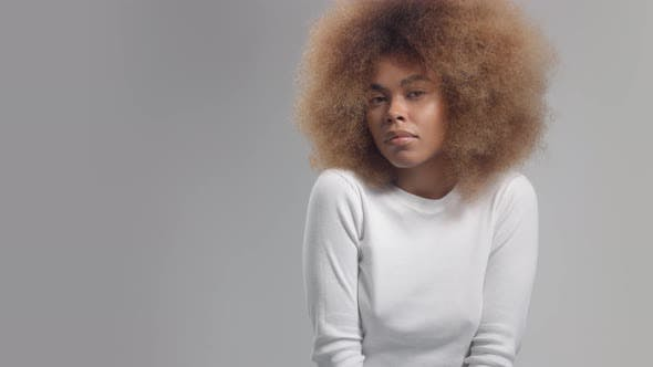 Panned Portrait of Mixed Race Black Woman in Studio Alone on Grey