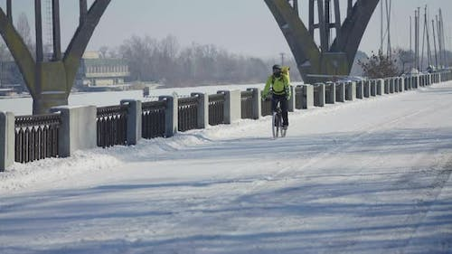 Man with Large Bag in Helmet Rides Bicycle Along Snowy Street and Delivers Food or Parcels