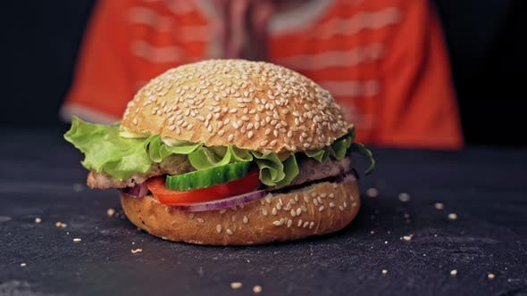 Thumbnail for Teenager Hands Take a Tasty Hamburger Lying on the Table