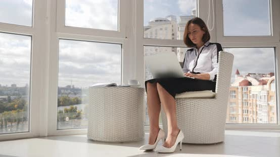 Thumbnail for Serious focused business woman in white blouse, black skirt and white heels working on laptop
