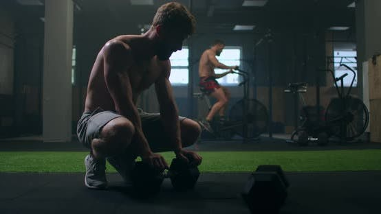 Thumbnail for a Male Bodybuilder After a Circular Cardio Workout Sits on the Floor of the Gym and Rest Gaining