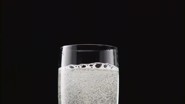 Thumbnail for Sparkling Wine Foams in the Goblet on a Black Background. Close Up