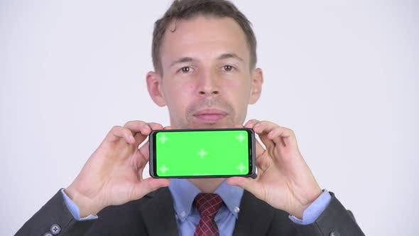 Cover Image for Studio Shot of Happy Businessman Showing Phone