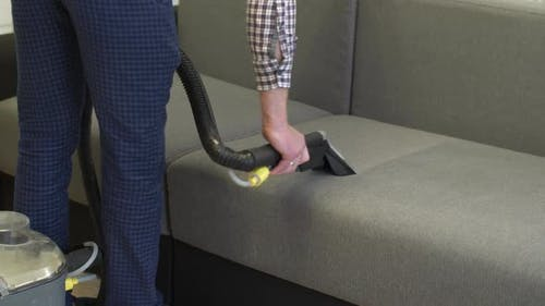 Man Cleaning Sofa at Home
