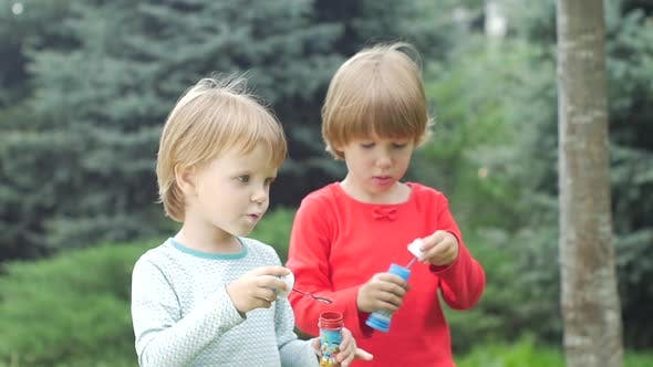 Thumbnail for Two Sisters Are Blowing Bubbles in the Park, Slow Motion. Close Up