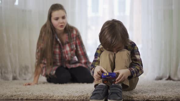 Thumbnail for Portrait Older Sister Scolds Younger Brother Who Is Playing with the Toy Car Sitting on the Floor on
