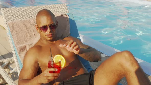 Thumbnail for Handsome African Man Drinking Cocktail Sunbathing at the Poolside