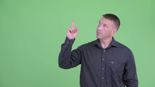 Thumbnail for Macho Mature Businessman Pointing Up and Giving Thumbs Up