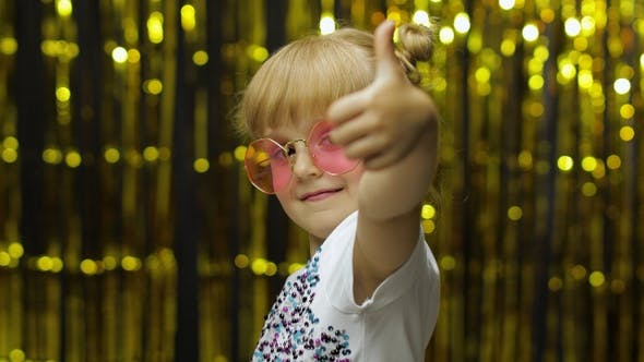 Thumbnail for Child Show Thumbs Up, Smiling, Looking at Camera. Girl Posing on Background with Foil Golden Curtain