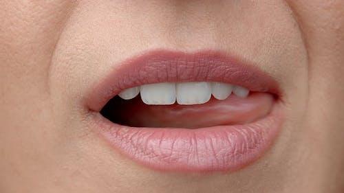 Woman Licks Her Lips Close Up. Gentle Female Tongue Licks Beautiful White Teeth