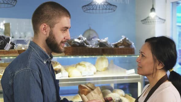 Thumbnail for Handsome Young Man Buying Fresh Bread From a Female Baker