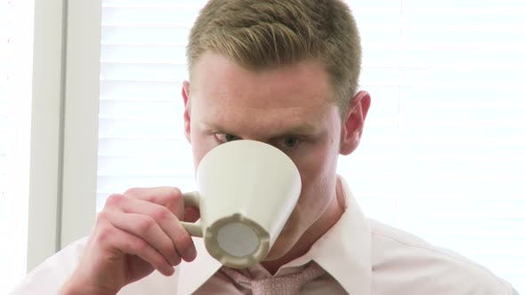 Thumbnail for Closeup of young businessman drinking a cup of coffee