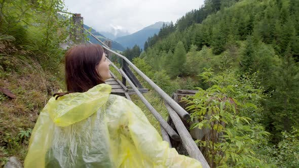 Thumbnail for Hiker in a Yellow Raincoat Traveling in a Mountain Forest