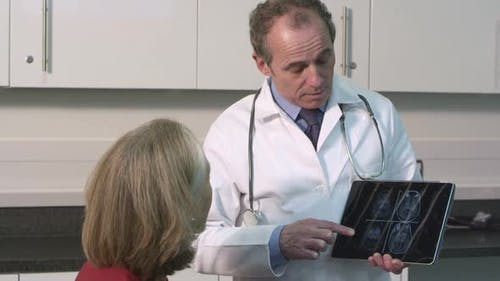 CU TD Male doctor using tablet discussing with senior patient in hospital / London, United Kingdom
