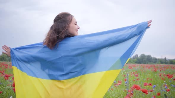 Thumbnail for Portrait Cute Young Girl Standing in a Poppy Field Covered with Flag of Ukraine