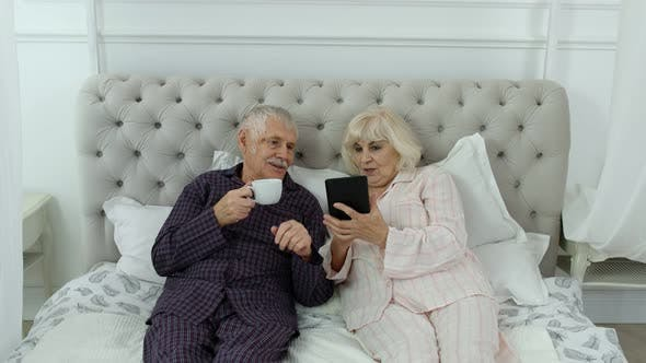 Thumbnail for Senior Elderly Couple Wearing Pyjamas Lying on Bed Looking on Digital Tablet Laughing and Having Fun