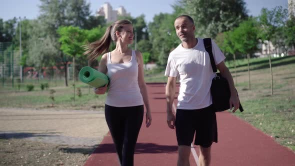 Portrait of Cheerful Caucasian Couple Strolling on Running Track After Morning Training. Happy Man