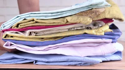 Putting Stack of Cloths on Table