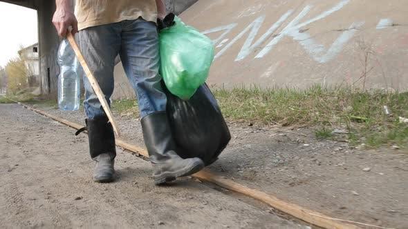Male Legs Scavenging for Plastic Bottle