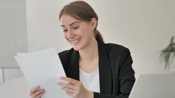 Cover Image for Young Businesswoman Reading Documents at Work