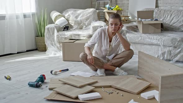 Cover Image for Tired Woman Looking at Disassembled Furniture