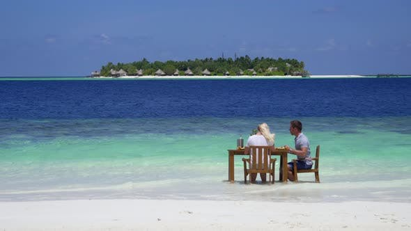 Thumbnail for A man and woman eat breakfast on a tropical island beach