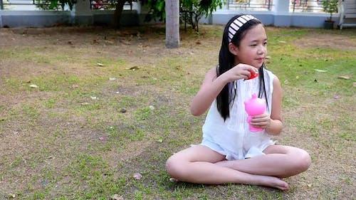 Cute Asian Girl Playing Bubble In The Garden