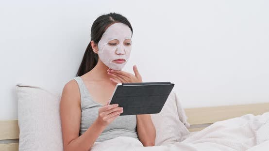 Thumbnail for Woman apply facial mask and watching on tablet at home
