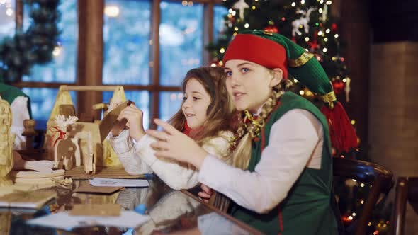 Thumbnail for An Elf in a Green Suit is Sitting at the Table and Talking About the Letters for the New Year