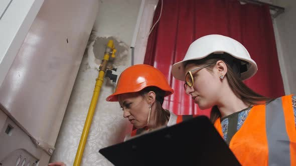 Two Women Checker Checking Technical Data of Heating System Equipment in a Boiler Room