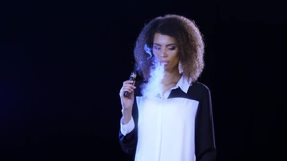 Thumbnail for Girl of African American Appearance Smokes an Electronic Cigarette, Black Background