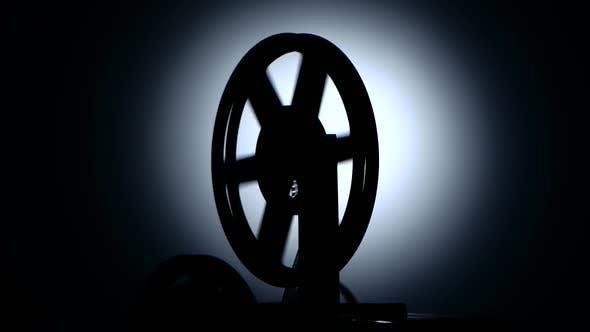 Silhouette in a Dark Studio. Bobbin Movie Projector Reels Film
