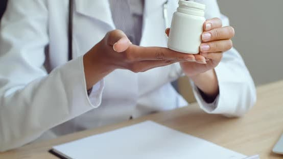 Close-up of Female Hands Passing Jar with Pills To Unrecognizable Patient. Doctor Giving Remedy To
