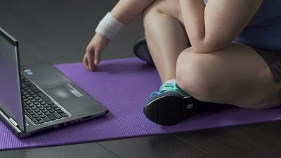 Teenager Watching Video on Laptop on Floor, Tapping Fingertips Against Yoga Mat