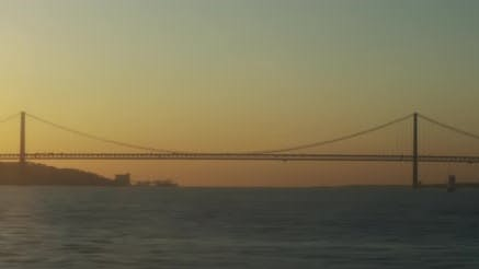 A boat view of an ocean bridge and a city port at sunset.