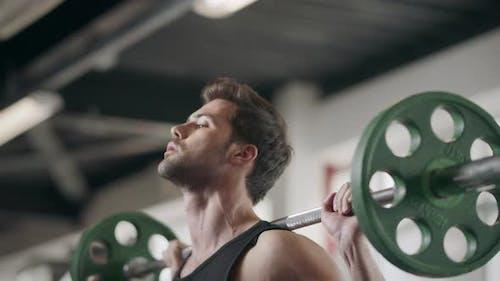 Bodybuilder Hocken mit Langhantel im Fitnessstudio
