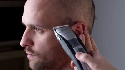 Hairdresser Shaves a Man Hair with a Hair Clipper.