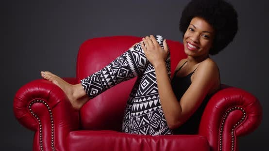 Thumbnail for African woman sitting in red armchair