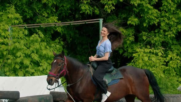 Thumbnail for Young Smiling Happy Woman with Long Hair in Blue Shirt Riding a Horse