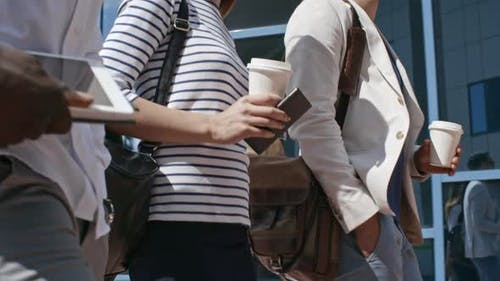 Mid-Section of Business People Walking with Coffee