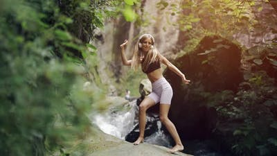 A Young Woman in Headphones is Listening to Music and Amusingly Dancing on Nature Background