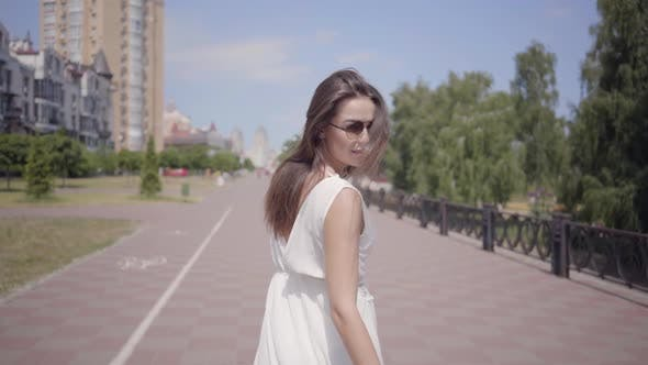 Cover Image for Glamorous Young Girl Wearing Sunglasses and a Long White Summer Fashion Dress Walking