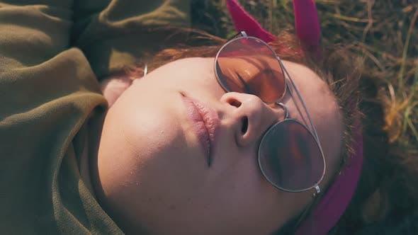 Young Woman in Orange Sunglasses Sleeps on Brown Meadow