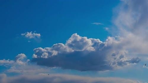 Blaue Wolken fließen in Zeitraffer am Himmel