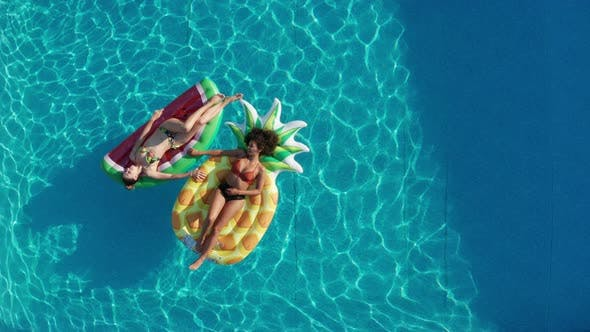 Aerial View of Young Women Floating in Pool