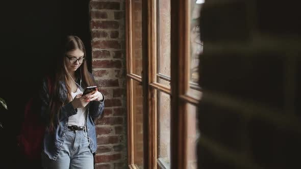 Thumbnail for Attractive Girl Standing By Window and Texting