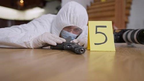 Waffe liegt auf dem Boden mit verschwommenem forensischem Wissenschaftler, der Beweise untersucht